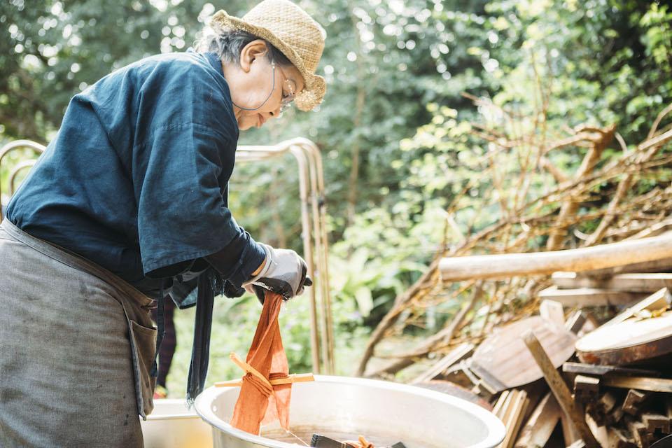 釜から挙げた布を水にくぐらせる石垣昭子さん。人間国宝である志村ふくみさんに師事した経験を持つ。