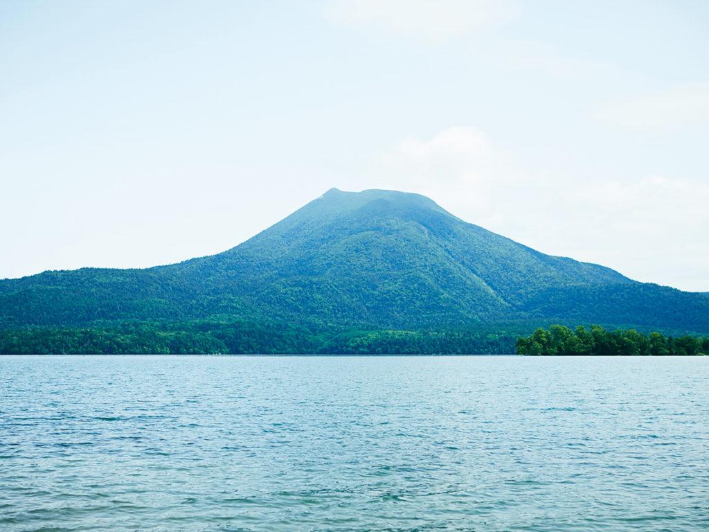 マリモが生育する湖から眺める雄阿寒岳。高さ1370mで、麓に温泉街が広がる。