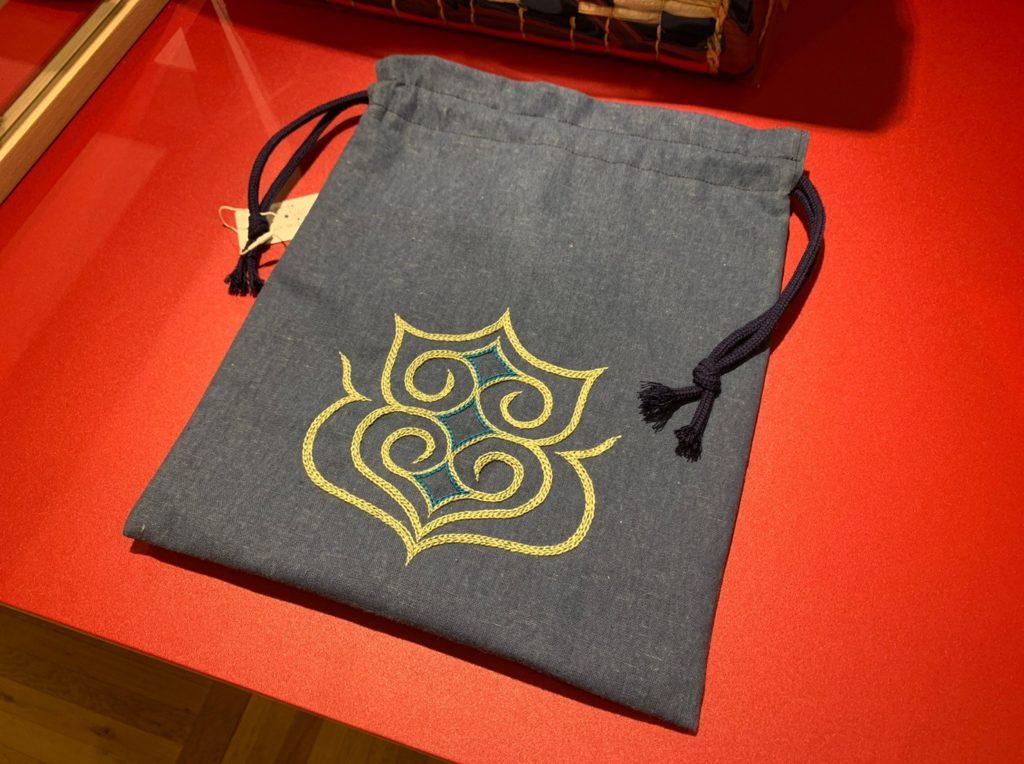 アイヌの文様を施した巾着袋は、刺繍作家の鰹屋エリカによるもの。独特ながら美しい色の組み合わせも魅力の一つ。