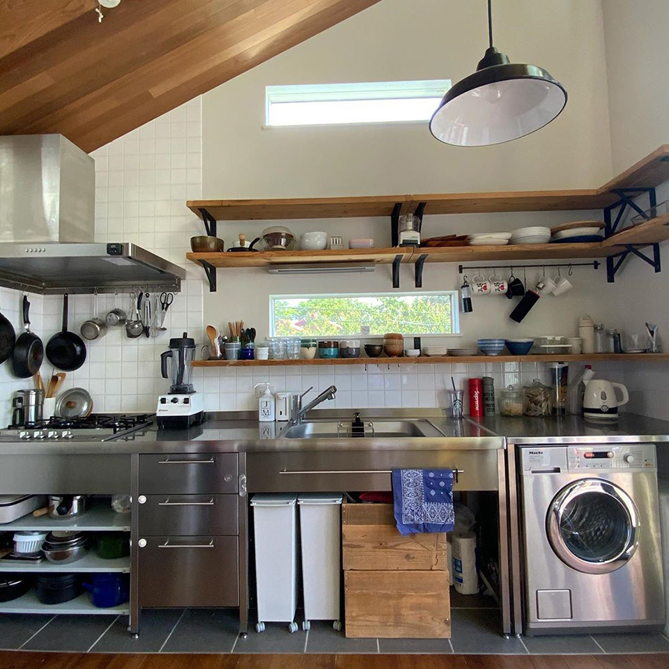 使い勝手のいい 台所と料理道具 Mieleの洗濯機の質感ともマッチしたステンレスキッチン 自然光がたっぷり入るので日中は照明いらず 目線の高さに作った窓からは季節によって表情を変える葉山の山々を望むことができます 食器や調理器具は隠さず棚に置いたり掛けたり 長く使えて気に入ったものだけに厳選してるので充分収まるしすぐに手が届くから意外と便利なんです