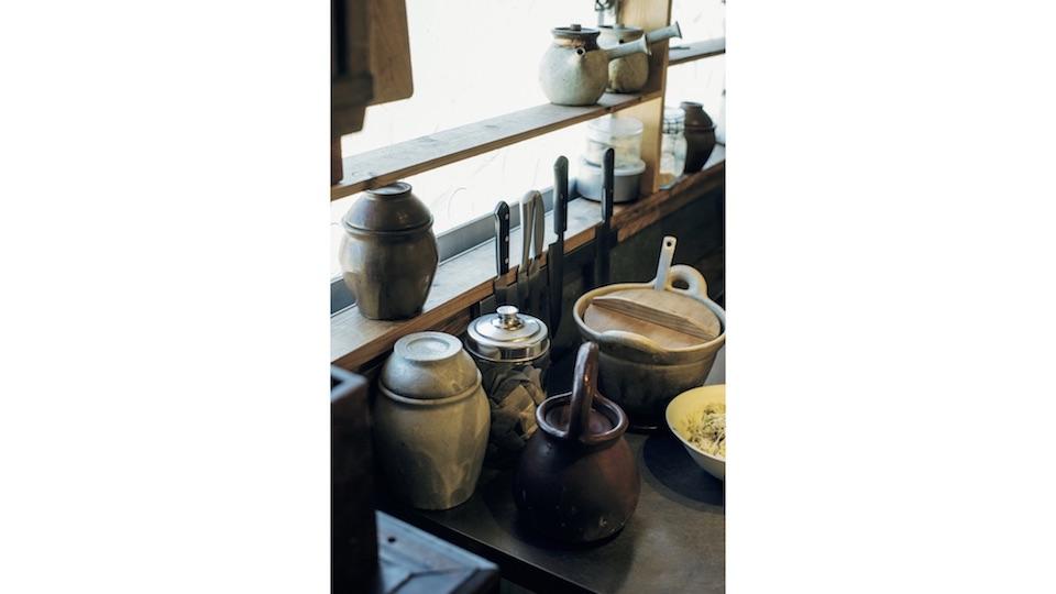 型板ガラスのレトロな雰囲気の窓辺に棚を自作。塩壺や調理道具などを配置した。