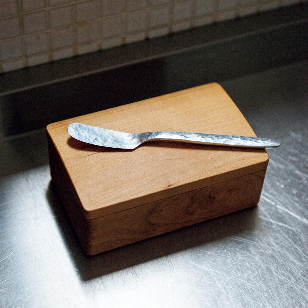 バターナイフ  笹倉 岳 熱伝導に優れたアルミ製のバターナイフ。「握った持ち手の熱が薄い刃先に効率よく伝わって、カチカチに固まったバターが驚くほど薄く削げる。ハンマーで凸凹に叩き上げながら、アルミをここまでシャープに仕上げる作家の技術にも惚れ惚れします。洗いやすいよう、片面を研磨している心遣いも」。桜の木で作られた、バターケースにもよく似合う。