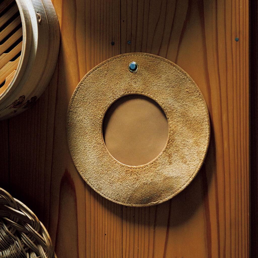 「ポッケ」革のミトン  キヅキ 木の壁にすんなりなじむ素朴な見た目。360度指が入り、熱い鍋ややかんが楽に持てるグリルミトン。適度な厚さで柔らかいため、ミトン越しでもものがしっかり掴みやすい。「牛革は使うたびに手になじみます。鍋敷きとしても使えるんですよ」。持ち運びしやすく、キャンプなどアウトドアのシーンでも活躍する。手入れして、革の表情を育てる楽しみも。