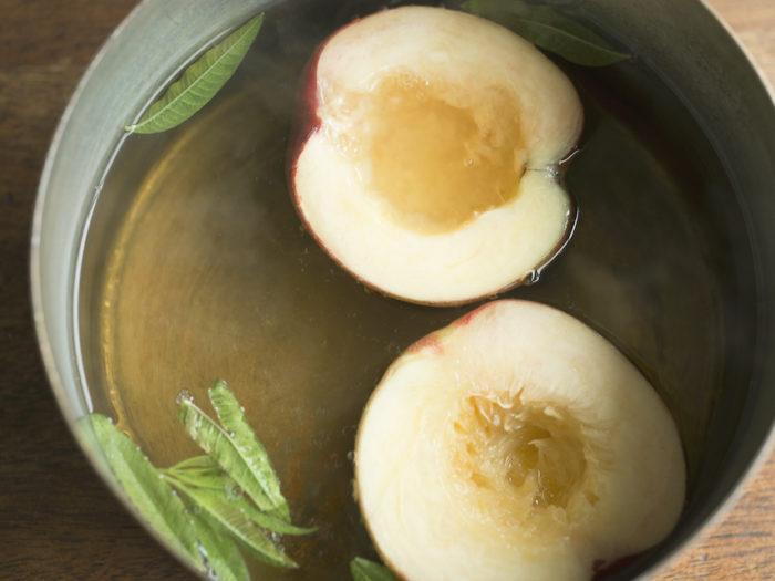 2.鍋に水ときび砂糖レモンバーベナを入れて火にかける。 沸騰したら弱火にし、桃の皮を下にして2分煮る。