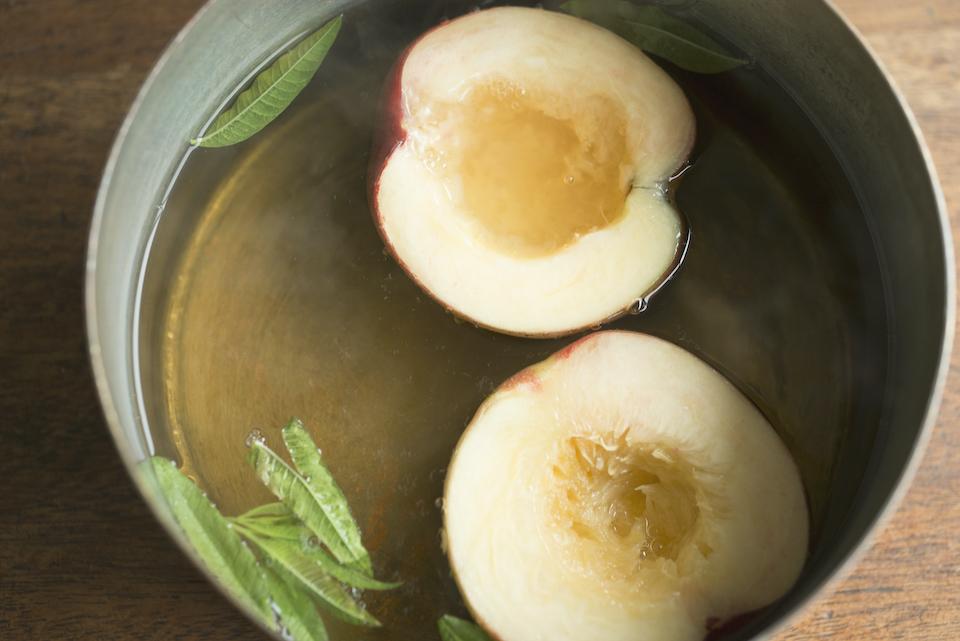 2.鍋に水ときび砂糖、レモンバーベナを入れて火にかける。沸騰したら弱火にし、桃の皮部分を下にして2分煮る。