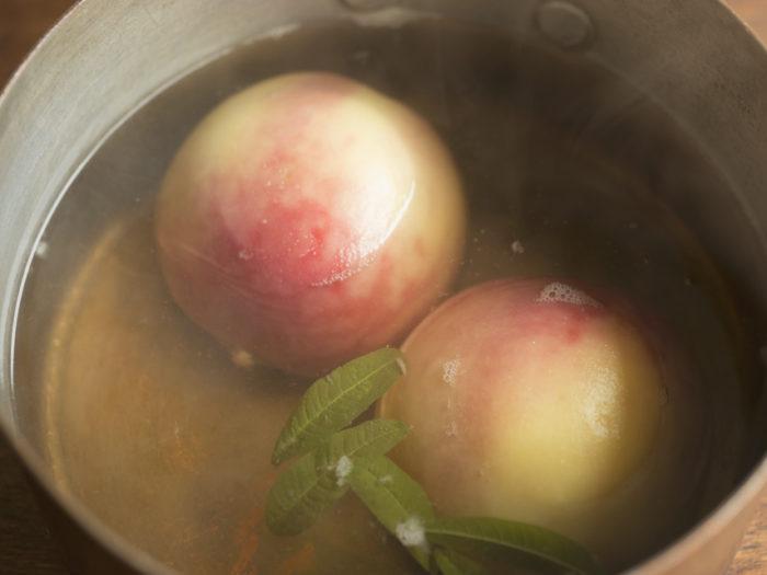 3.桃を裏返しレモン汁を加える。さらに2分煮たら火を止 めボウルに移し、粗熱が取れたら皮をそっとはがす。
