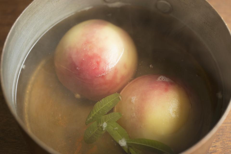3.桃を裏返しレモン汁を加える。さらに2分煮たら火を止めボウルに移し、粗熱が取れたら皮をそっとはがす。