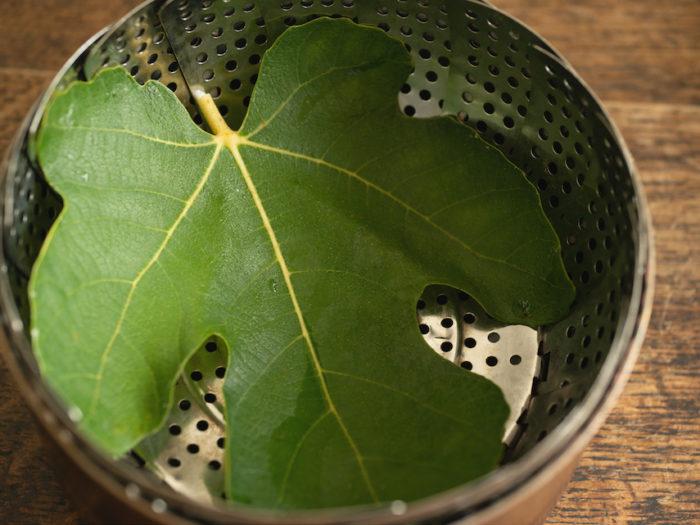 2.鍋に簡易的な蒸し器を置き、イチジクの葉を敷く。