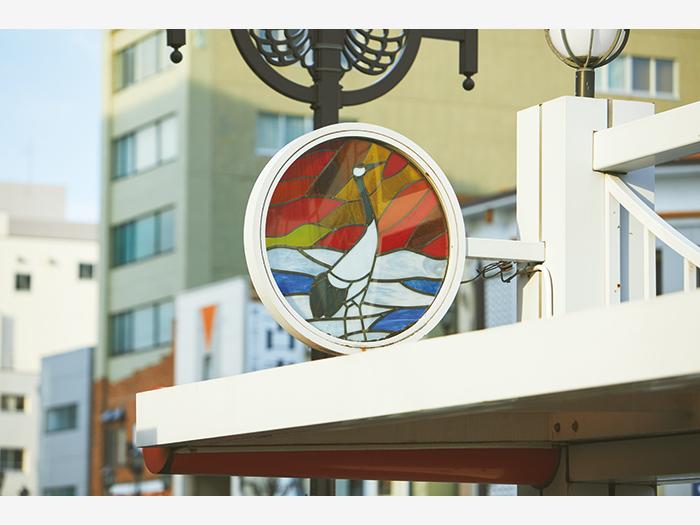 バス停「十字街7丁目」のステンドグラス。マンホールや街灯などにタンチョウがあしらわれている。
