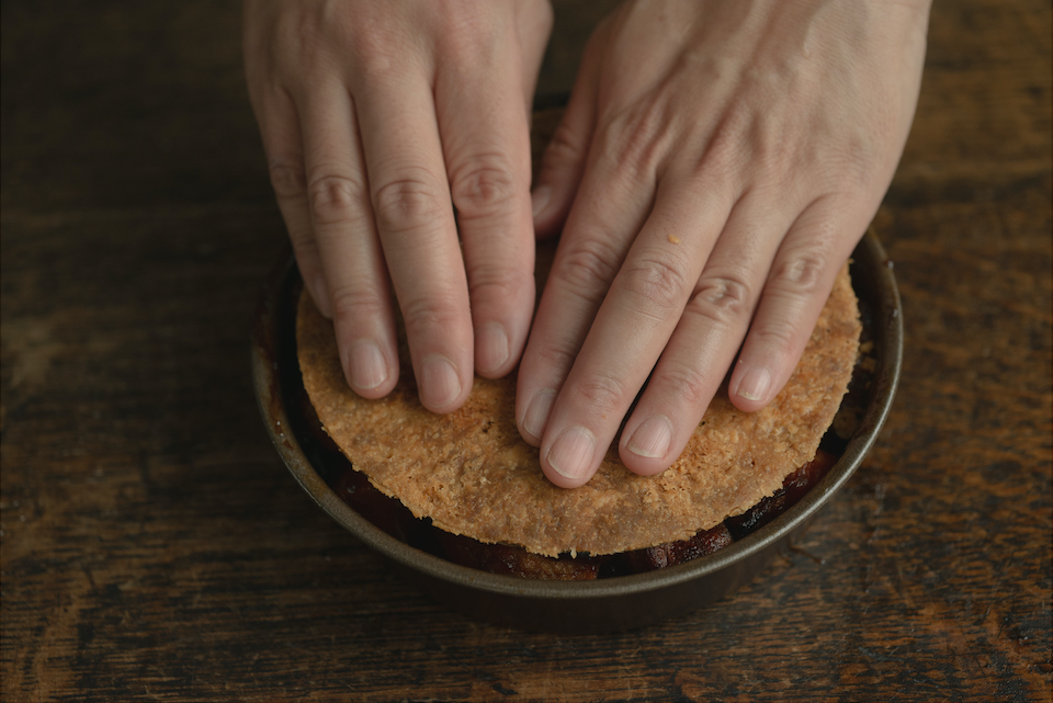 8 焼きあがったフィリングに3の生地をかぶせて優しく押さえ、リンゴに含まれているペクチンで接着させる。粗熱をとり、冷凍庫に入れて固まったら、型の周りを湯煎などであたためて、側面をナイフでぐるりとし、ひっくり返して型から出す。