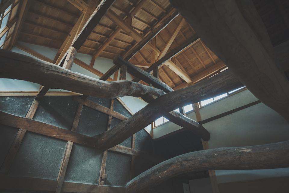改修によって、70年以上の歴史を 持つ梁の存在が明らかに。天井を高く上げ、たっぷりと採光を確保している。時を経た格子状の土壁と、新しい白壁とが対比をなす。