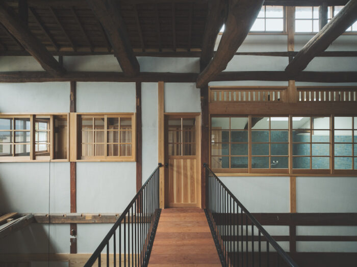 2 階寝室から、渡り廊下ごしにガラス窓のある風呂場と更衣室を見る。階下はギャラリースペース。