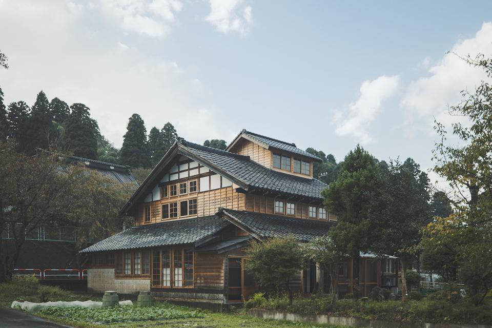 日本家屋でここまで窓の多い外観は珍しい。住居兼工房だった築70年ほどの古民家を、5 年をかけて改修した。寺と里山を背にし、周囲に「流動研究所」の工房や作業場がある。