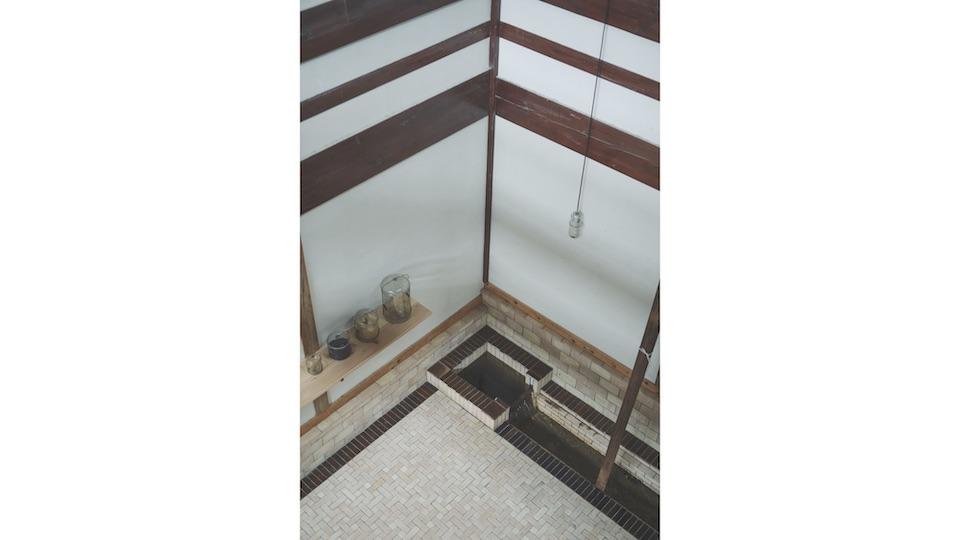 2 階の渡り廊下から1 階のギャラリースペースを見下ろす。床のタイルは風呂場と同じモロッコのタイル。家の中に水路があり、絶えず水の音がさやかに流れている。
