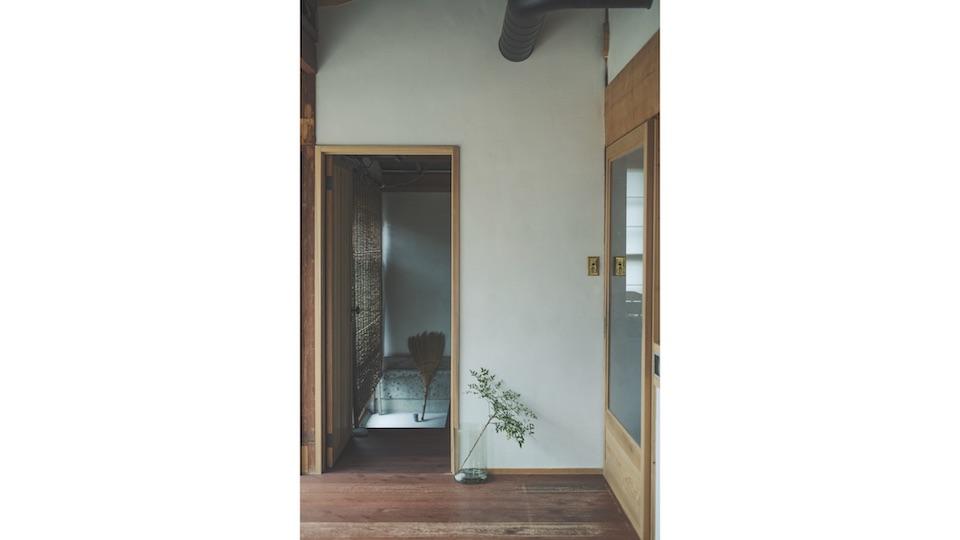 1 階の洗面所とベンガラ塗装を施した板廊下。右手がキッチン、左手はサンルームに。