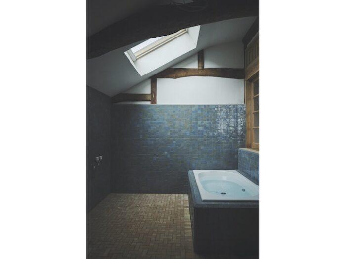 2 階にある風呂場。梁を残し、モロッコ製のタイルを張った。天窓と内廊下から光を取り込む。