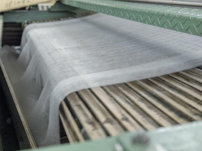 紡績の中間過程。カード機で繊維を揃え、長さを揃えて太いひも状にする。糸の前の篠(しの)を作る。