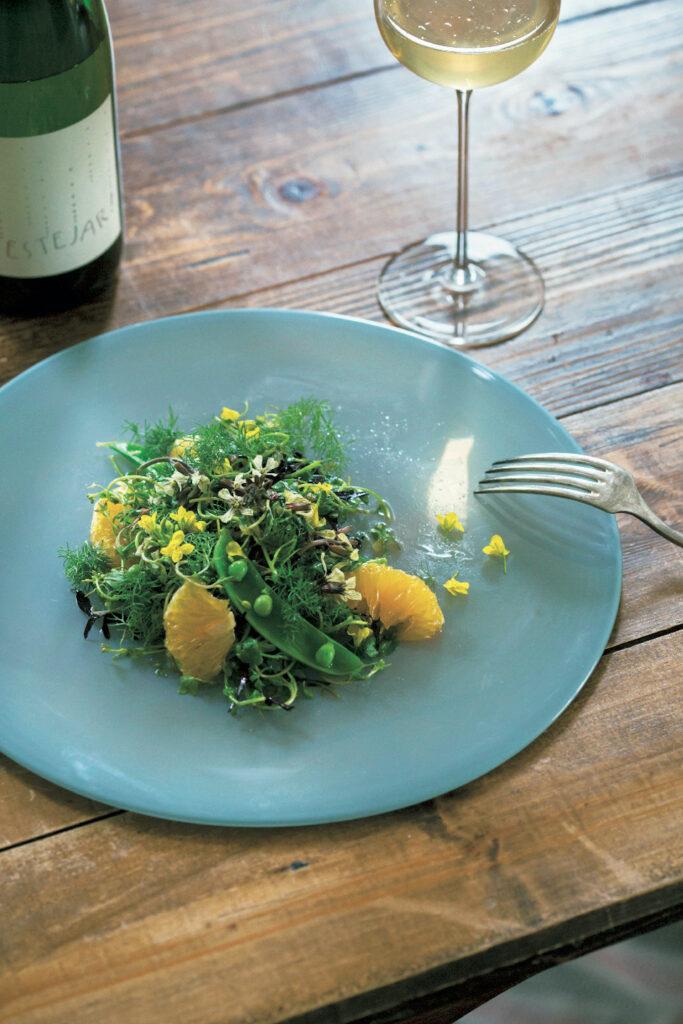 「大きな器から買う性分です(笑)」と鈴木純子さ ん。ガラス作家・辻和美の大皿は、澄んだ湖のよ うな水を感じさせる涼やかな色。定期的に取り寄 せている『ポム・ド・テール』の有機野菜とハー ブ、柑橘を和えたサラダを盛り付けて。