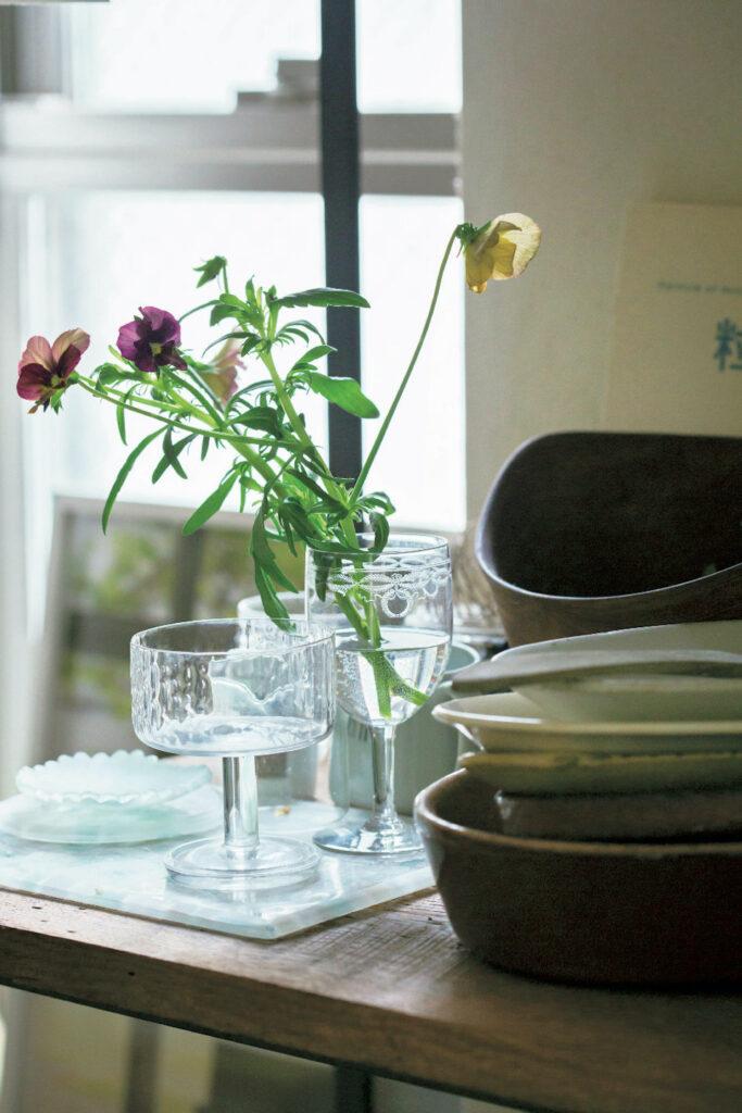 小さな頃から草花とともに暮らす日常を過ごして きた鈴木さんは、野に咲くような花を 1 種類でバ サッと生けるのが好み。フランスの蚤の市で「レ リーフの美しさや繊細な佇まいに惹かれた」とい うアンティークグラスには、大好きなヴィオラを。