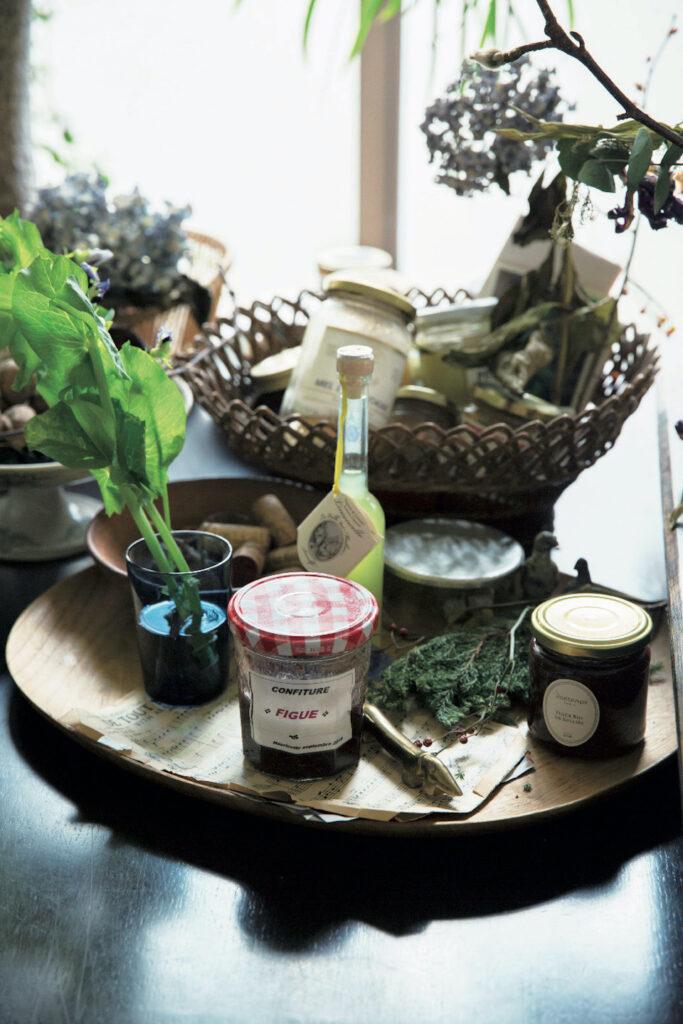 手仕事で作られたカゴや安彦年朗のウッドトレー を配置したキッチンの空きスペース。ティモ・サ ルパネヴァによる〈イッタラ〉のブルーのヴィン テージタンブラーには、サラダに使ったスナップ エンドウの花をラフに生けた。