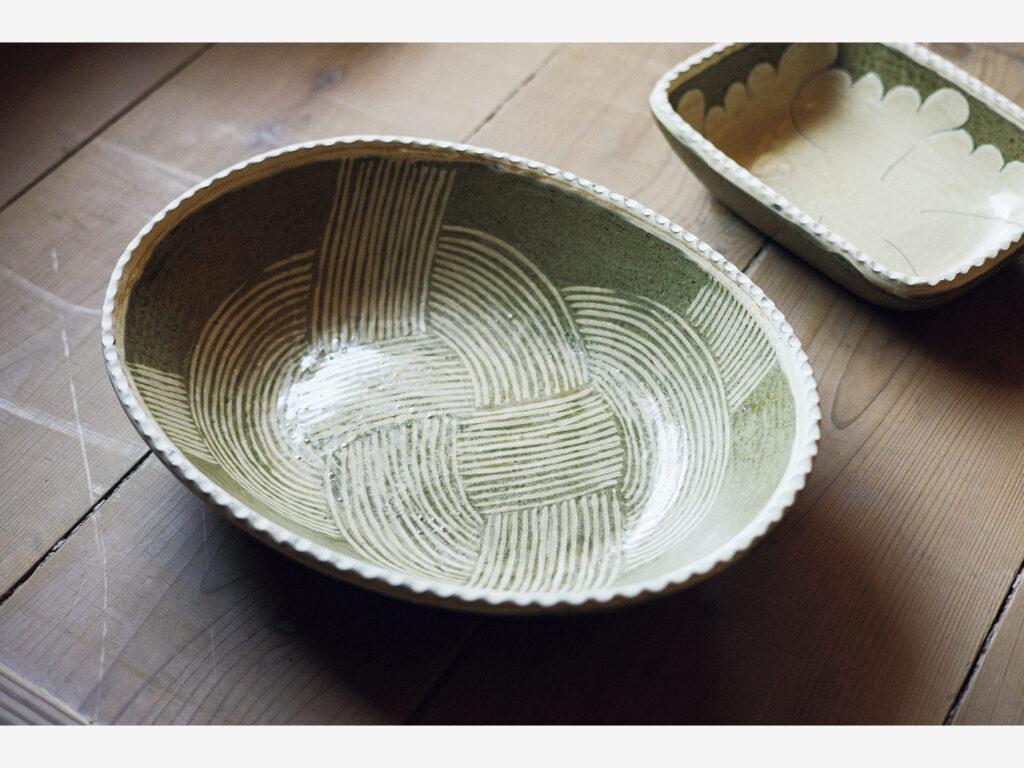 手前から象嵌(ぞうがん)楕円鉢・結び文、掻落(かきおとし)角鉢・牡丹柄。器を削って文様を描き白い土を埋めて仕上げる象嵌、牡丹の花をモチーフにした掻落は山本さんの代表作品のひとつ。