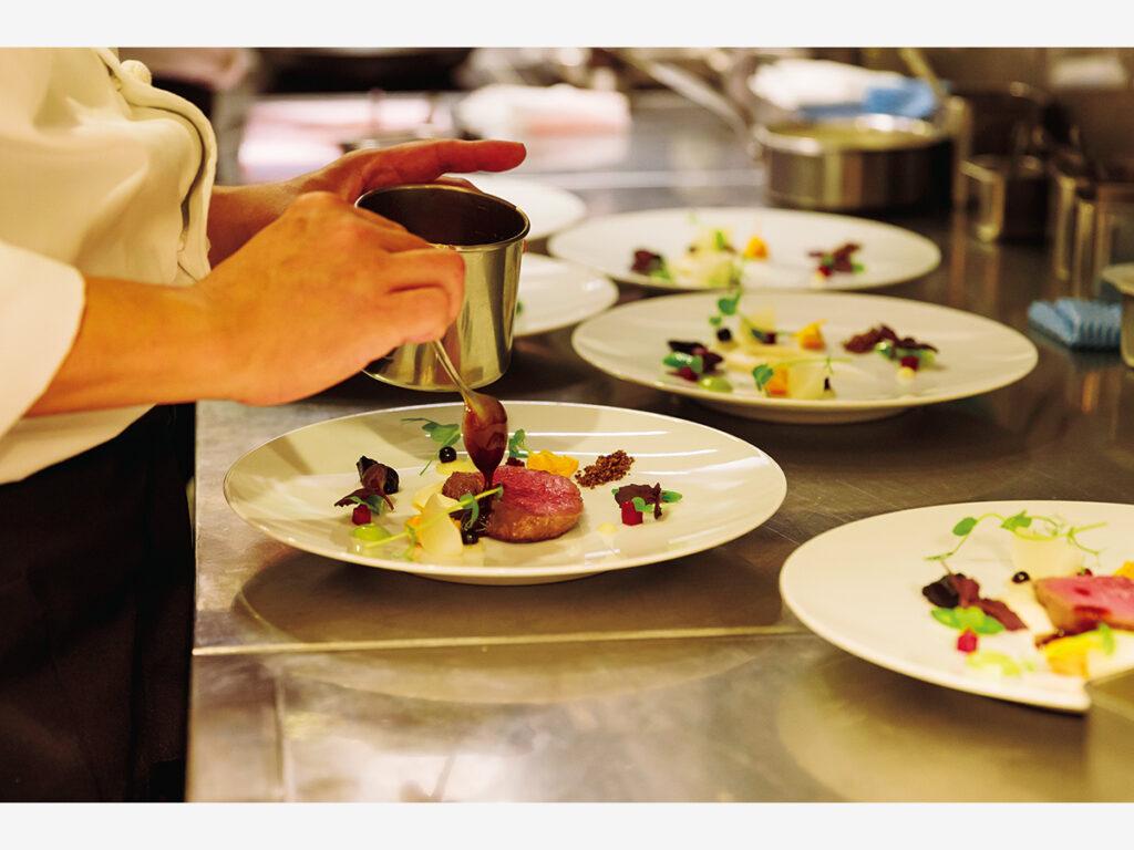 食堂車にはオープンキッチンが設けられ、調理の様子を間近に見ることができる。調理中の料理はレストラン『ハジメ』オーナーシェフ米田肇が監修する「希望」。