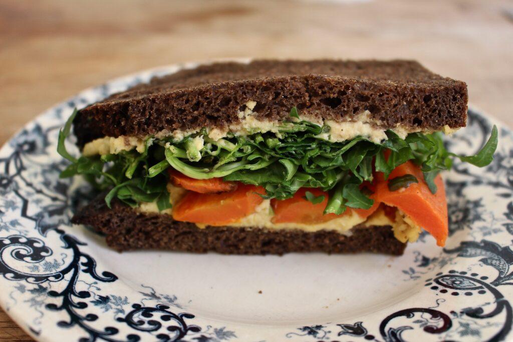 ライ麦パンで、フムスとルッコラに人参のローストを挟んだ野菜サンド。ニンニクを効かせたフムスがソースの役割も果たしていた。フォカッチャで作るベジサンドもある。