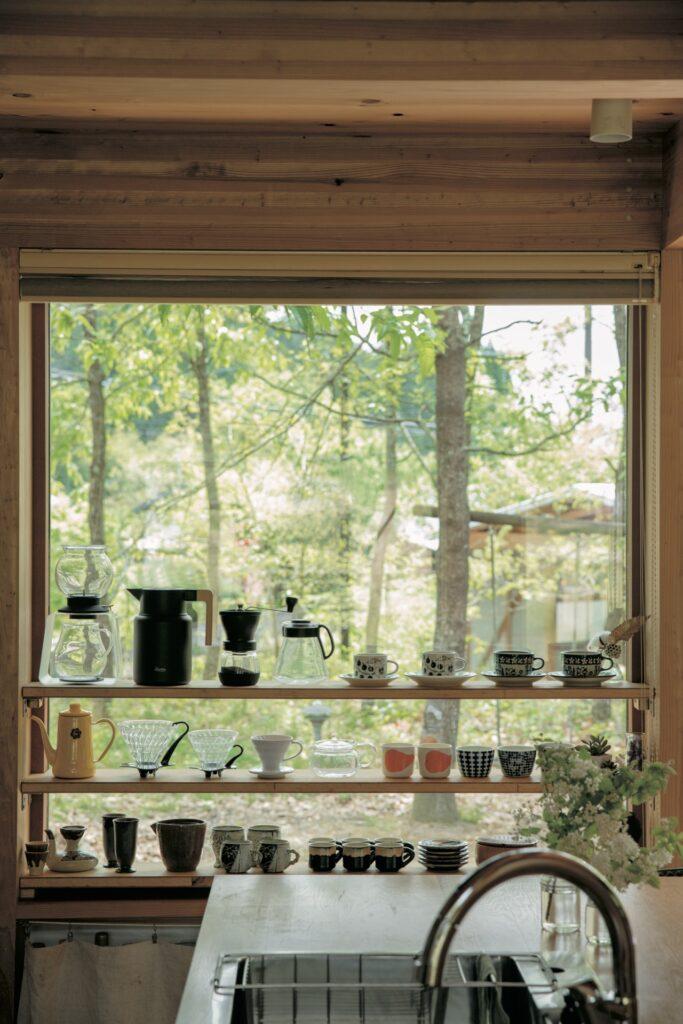 加賀江夫妻が暮らすリビングの窓辺。1.5×1.5 mの大きな窓にDIYで棚板をつけて、緑豊かな景色を見 渡せるスペースにお茶の道具を並べた。