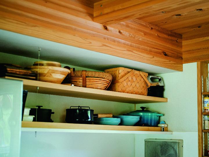 コンロ台の壁にシナ合板の棚板を 2 段固定。木の温もりを感じるカゴやザル、ミ ントブルーの〈イッタラ〉の皿や〈シャスール〉の鍋など美しい道具を陳列。