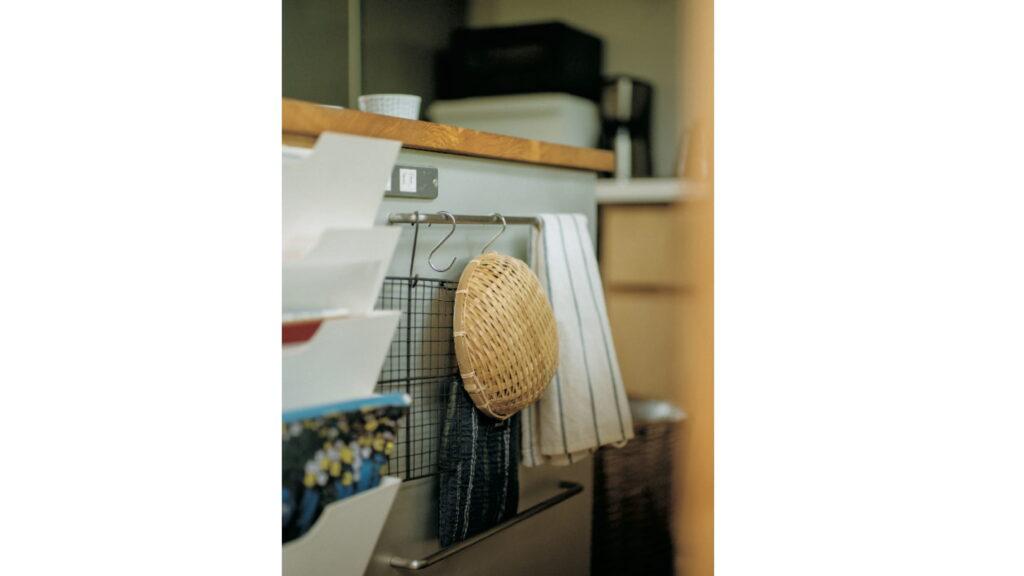 アイランドキッチン脇にラックやタオルハンガーを取り付けた。よく読む料理本、調理道具などをまとめて。