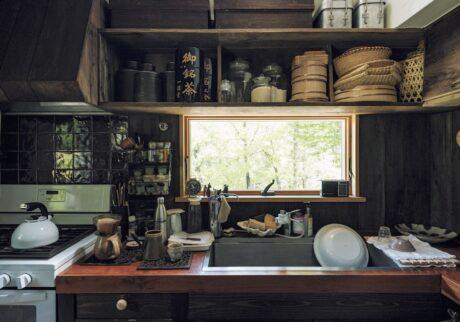 栃木県益子町にある『Loveit』店主のはったえいこさんの台所。窓からは四季折々の景色が楽しめる。森をイメージし、台所は茶系でまとめた。上 の棚には、愛飲するお茶の缶、米、小麦粉などの ほか、おひつやザルなど毎日使うものを収納。