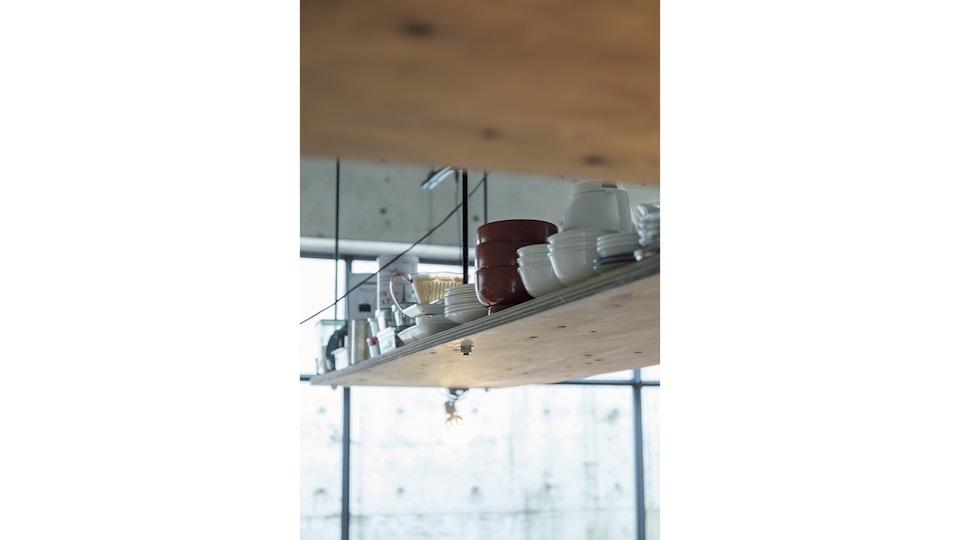 天井から吊ったベニヤ板が収納スペース。ふだん使いの食器が並ぶ。
