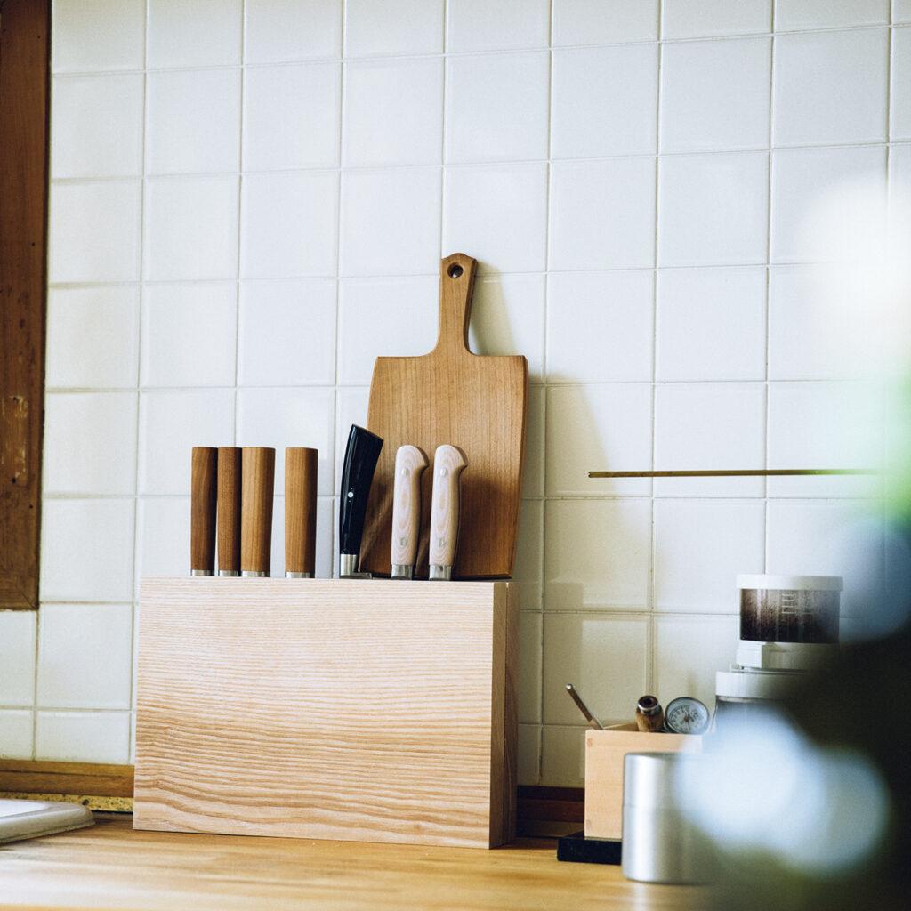 ナイフブロック  サイド バイ サイド 無垢の木を張り合わせたナイフ立ては、オブジェのような存在感を放っている。「木の塊がキッチンに、どんとあるのがなんとも洒落てるなと。今ではそこにないと寂しい感じで、安心感もある。レシピ本やカッティングボードも立てられるしね」。キッチンの水回りで使うからと、表面をカンナ仕上げにカスタマイズして、どう変化するかを観察中だという。
