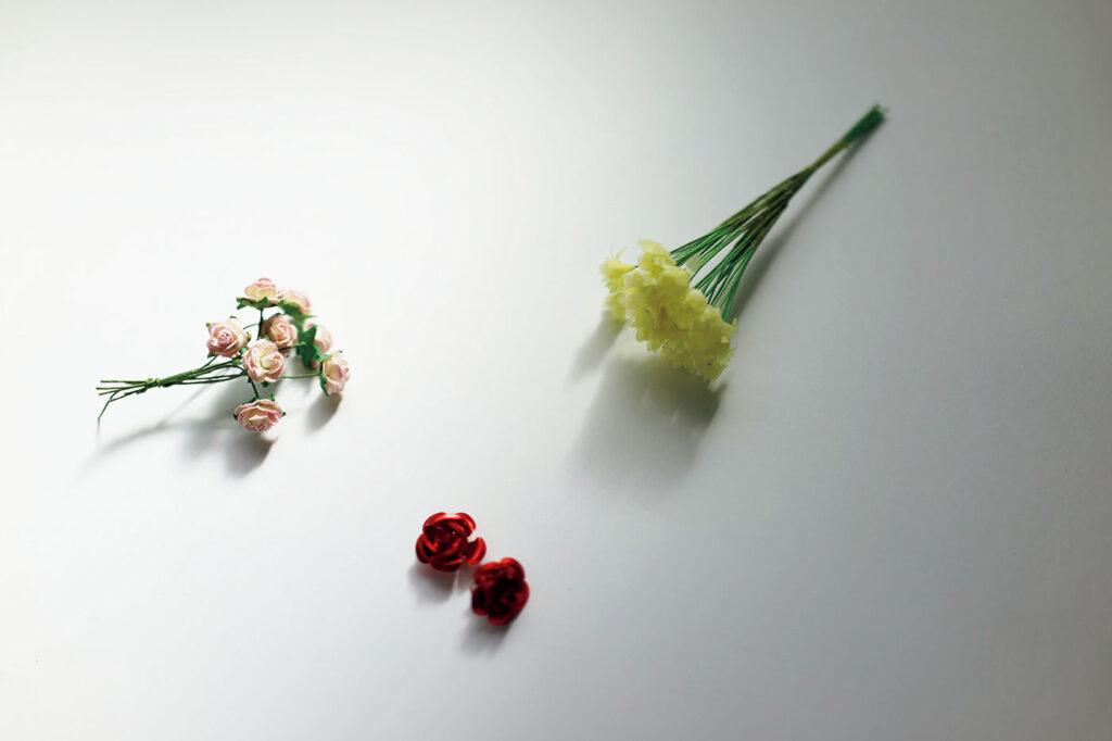 ペーバーフラワー 小林エリカ 文房具 トラベラー 左/ベトナムの古びた文房具屋の片隅で発見した薔薇の花。中/エストニアの古都・タリンの文房具屋で売られていたのは金属製のシールタイプ。右/渋谷PARCOの〈POV STORE Bangkokシテン〉にて入手したタイの花。
