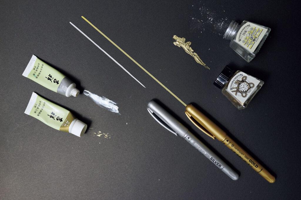 左/絵の具は〈吉祥〉の日本画材料顔料が好き。赤金もあり。中/友人から教えてもらったチェコ〈centropen〉の水性金銀ペンは発色も使い勝手も最強! 右/英国の〈WINSOR & NEWTON〉のインク壺シリーズの可愛さは無敵。小林エリカ フォルダ 文房具 トラベラー 金銀