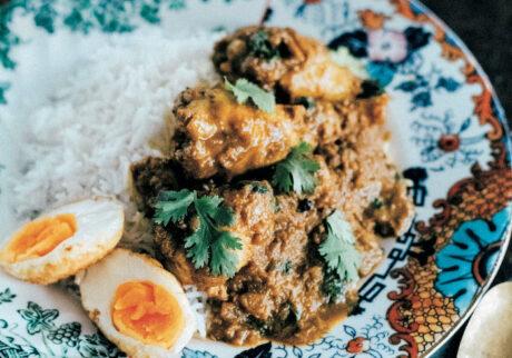 ヨーグルトや薬味、スパイスでじっくりマリネした手羽元のカレー。お好みで揚げ卵とパクチーをトッピング。