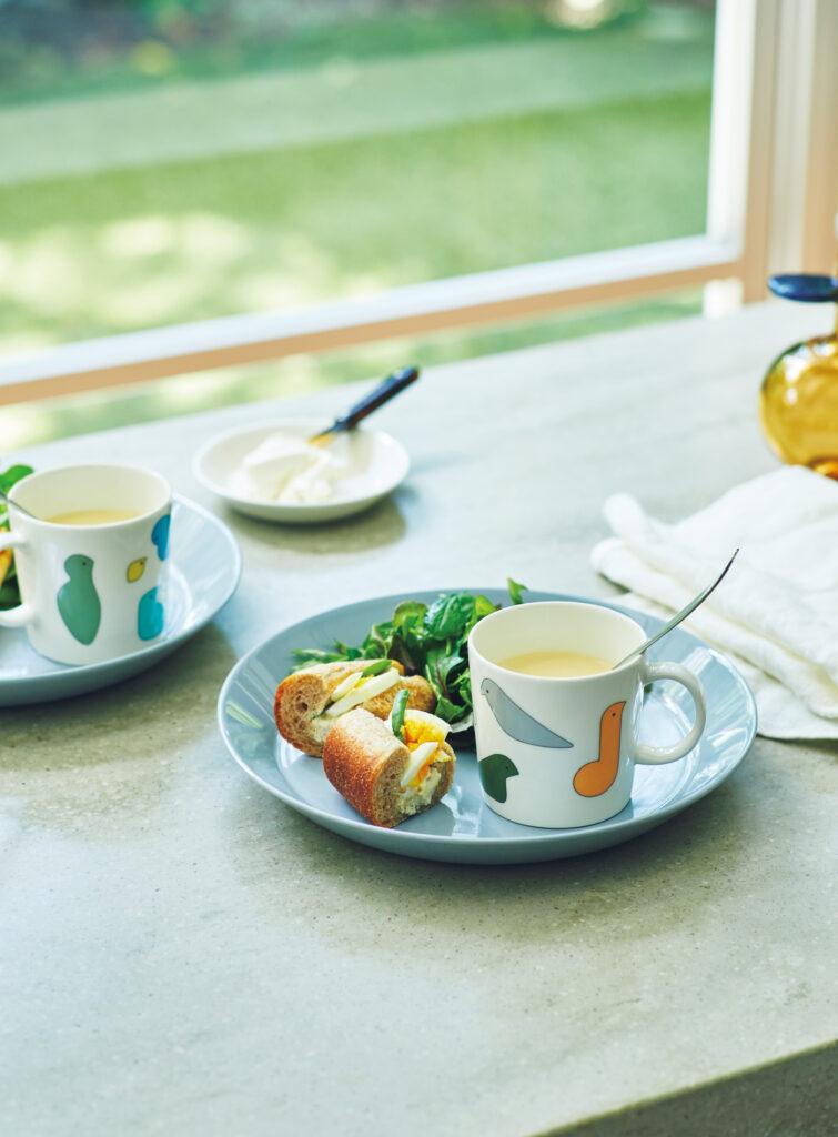 色とりどりの7羽の鳥たちが彩るマグカップは、みずみずしい食卓によく似合う。マグカップ各¥3,080、プレート[∅12㎝]2枚セット¥3,300(以上イッタラ×ミナ ペルホネン) プレート[∅26㎝]各¥3,850、スプーン各¥1,430、ガラスオーナメント¥38,500(以上イッタラ)