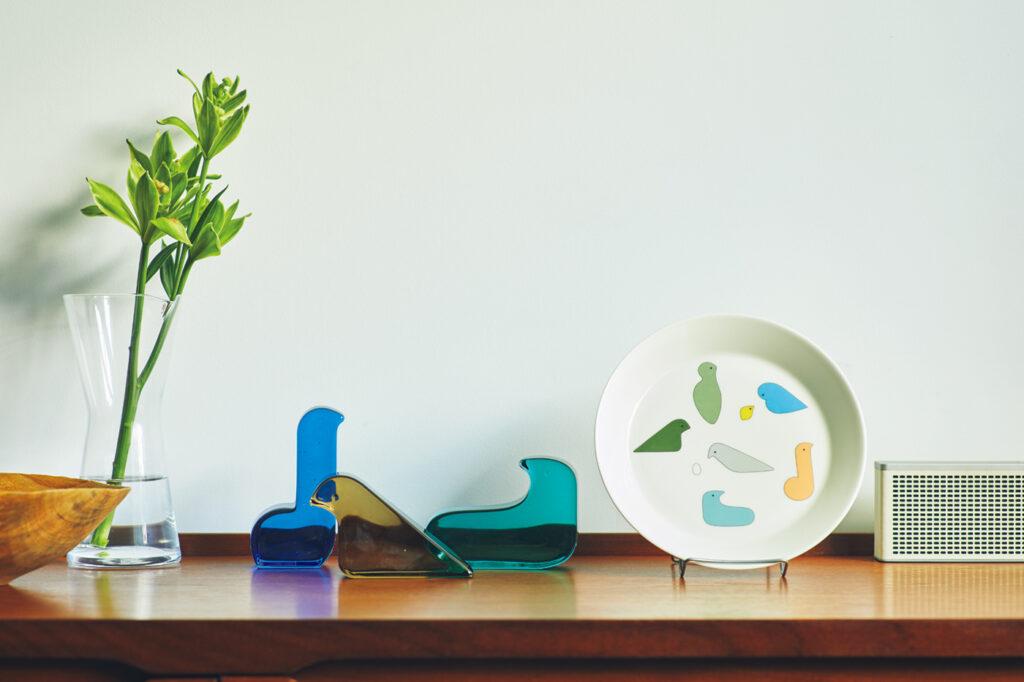 ガラスの色は「暮らしの中で光とともにあることをイメージし、そして集うように置いたときに響き合うように選びました」と皆川さん。大きなプレートは飾ってもまた美しい。 プレート[∅21㎝]¥3,080、ガラスバード各¥8,250(以上イッタラ×ミナ ペルホネン) カラフェ¥9,350(イッタラ) その他スタイリスト私物