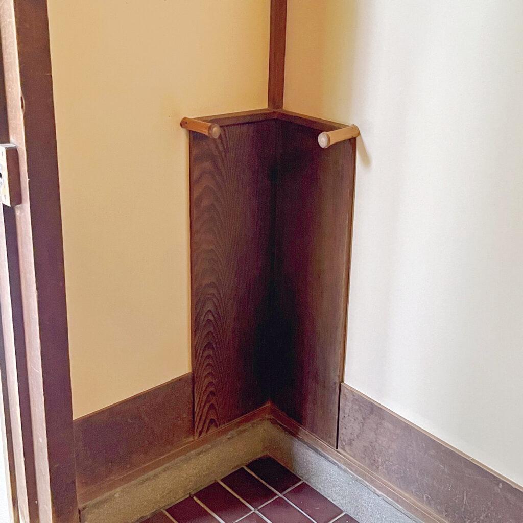 """「聴竹居(ちょうちくきょ)」玄関の隅を立派な傘立てに  仕立てる、二面の壁から飛び出る竹。 建築家・藤井厚二が5回目の自邸として昭和3年に竣工。「強く感じるのは空間を広げるための、部屋の隅への意識。傘立てなど多くある造り付けの""""もの""""は、建築に収まった彫刻作品にも思えます」"""