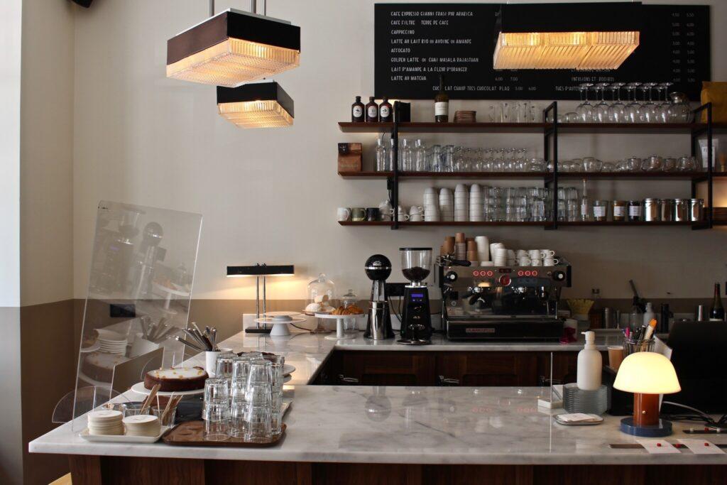 """カウンターの上に設えたランプシェードは、前の店『カフェ・トラマ』で付けていたものと同じモデルにした。「常連さんたちが、場所は変わったけれど、馴染みの店に""""帰ってきた""""ような気分になれるように」"""