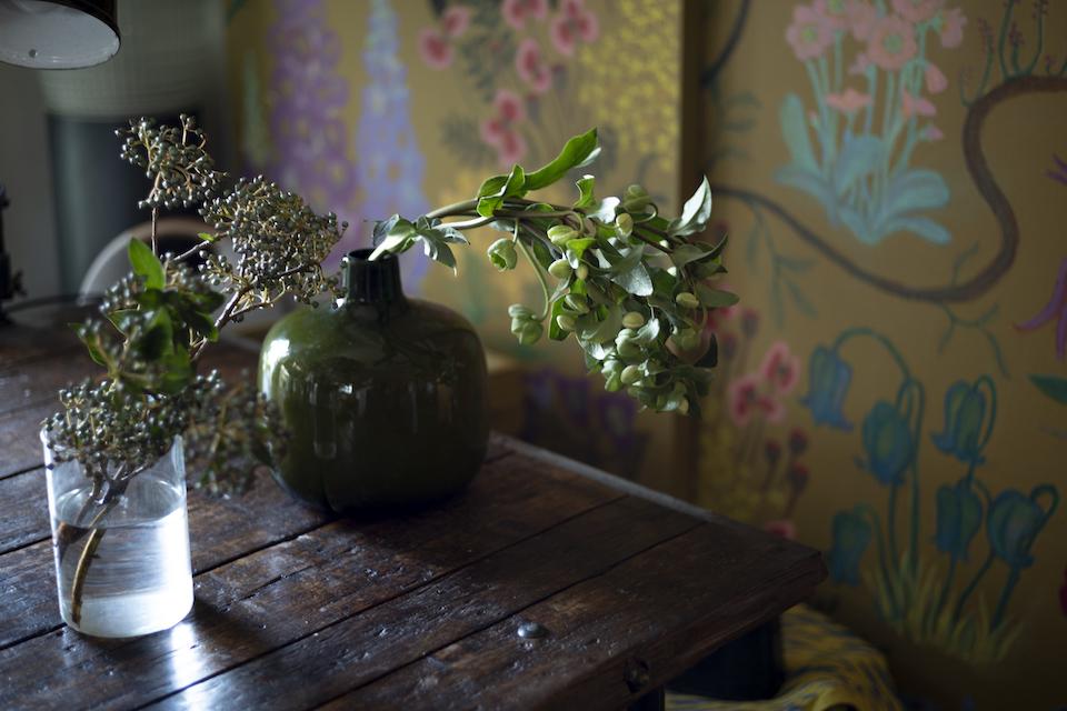 部屋に飾られた花の中には、摘んできた草花も。背景の花柄は、個展のために自身が描いた備品。