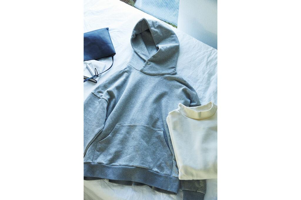 大きなフードと首元のボタンに、余裕のある肩まわり。一枚で様になるパーカは、裾はスマートに仕立ててあるのでコーディネートに馴染む。モックネックスウェットも同様のシルエットで、度詰めの生地が形を際立てる。パーカ¥16,500、スウェット¥12,100(ともにハーベスティ/ハーベストムーン)