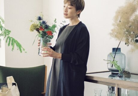 大切な人に花を贈ることも好きだけれど、自宅でもさまざまな場所に花を欠かさないようにしているという高山さん。「花を飾ると、忙しくても穏やかでいられます。 花の色に合わせてコーディネートを決めることもありますね」。リラックスフィットで着心地がいい膝丈のロングカーディガンとフレアシルエットのワンピースのレイヤードスタイルは、ワンマイルウェアとしても活躍。「私の定番シルエットです。シルエットが美しく、形崩れしにくい。手入れのしやすさも高ポイントですね」 オーバーサイズカーディガン¥17,600、ワンピース¥19,800、椅子に置いたエコバッグ¥3,300(以上UNOHA)