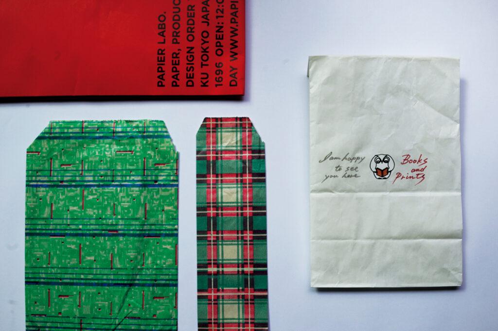 左上/千駄ヶ谷の〈パピエラボ〉。さすが上質、 3色揃えたい。左下/アルゼンチン土産の紙袋 が可愛すぎ。右/写真家・若木信吾さんの浜松 にある本屋〈BOOKS AND PRINTS〉は、お 父様・欣也さんによる一つずつの手書き!
