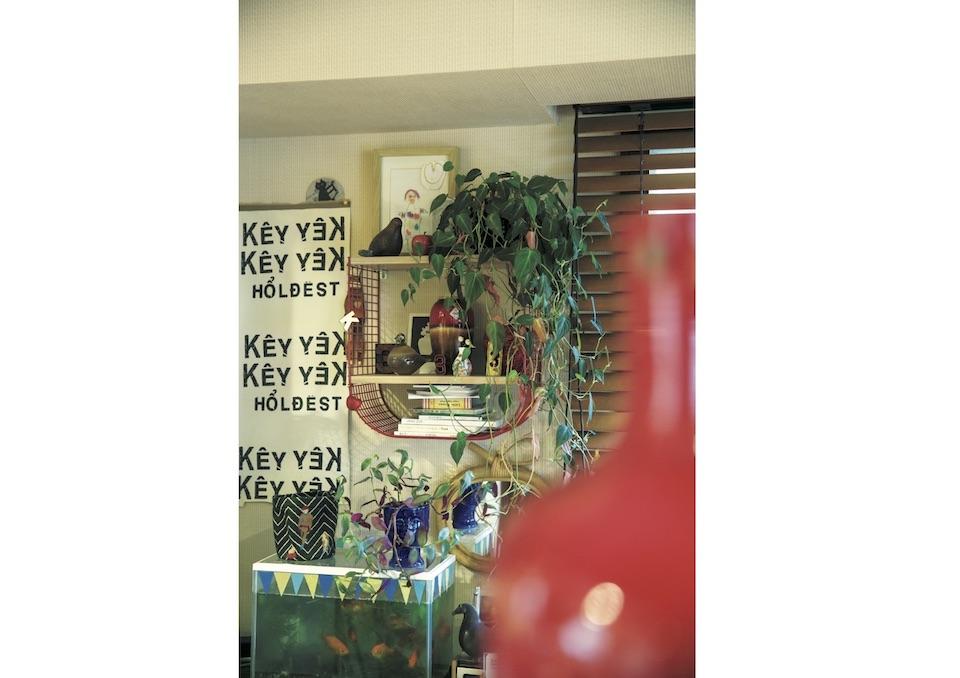 ダイニングの壁には、子どもの絵や水槽な ど、空間を埋めるように小物が並ぶ。グリ ーンは近所の昔ながらの生花店で購入。