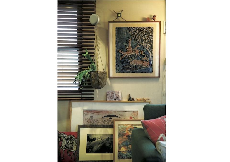 アートは立てかけて、重ねて。壁に掛けたのはデンマークの陶芸家アクセル・サルトのリトグラフ。額の上にも小物が。