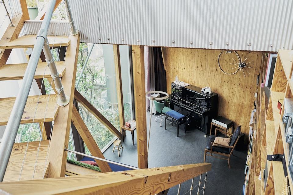 外壁用の素材を屋内に使用して、庭との境目に壁を作らず、窓やドアで構成している。