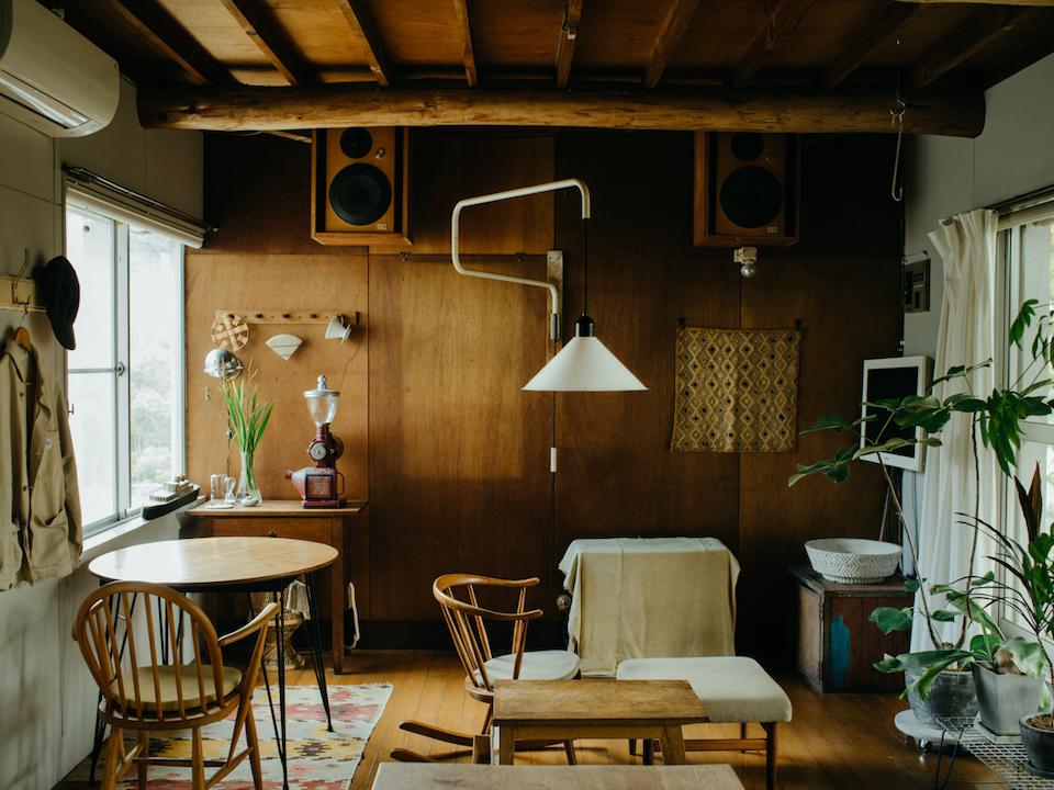 リビングの反対側の壁にはベニヤ板を張り、天井と壁まわりの色を統一。ロッキングチェアを置き、寛げる空間を意識した。窓際にはコーヒーを淹れる道具をまとめたコーナーも。
